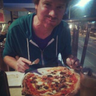 Mike enjoys his pizza.